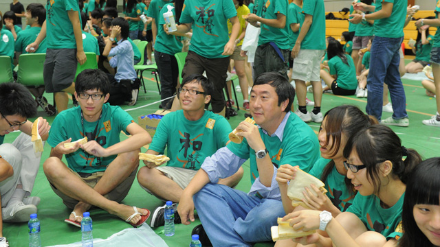 Prof. Joseph J.Y. Sung, Vice-Chancellor, consumes bread and water at the Rich and Poor Men's Banquet at the Lee Woo Sing College orientation camp.